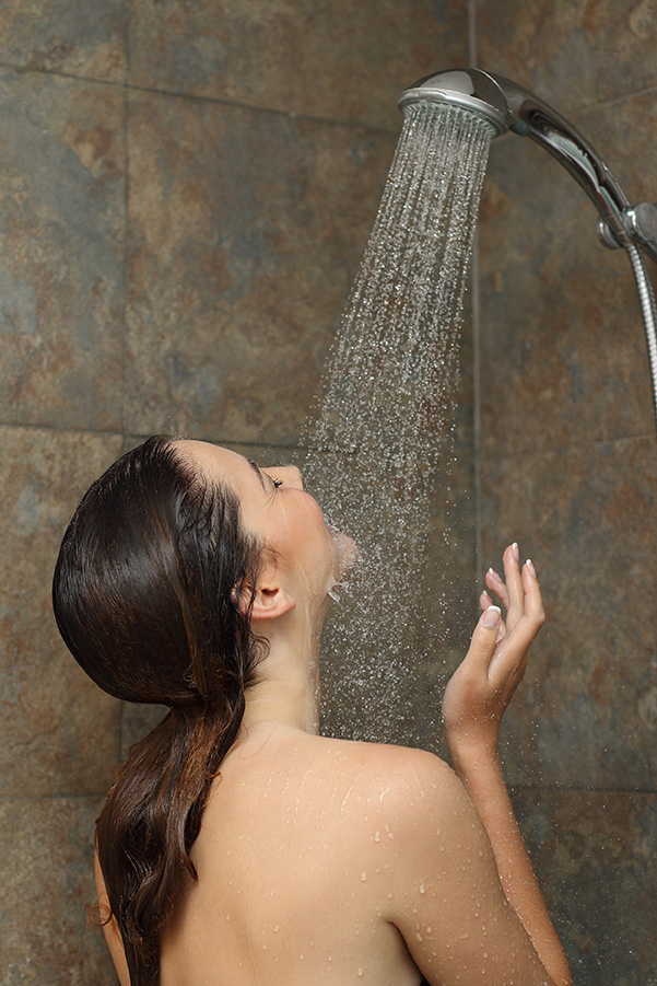 Woman enjoying the water in the shower under a water jet
