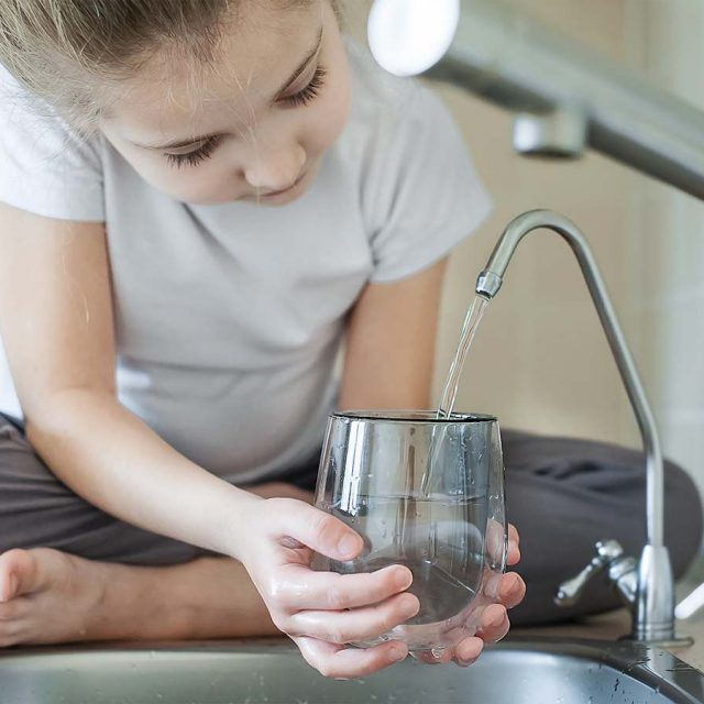 Little girl using a R/O water tap